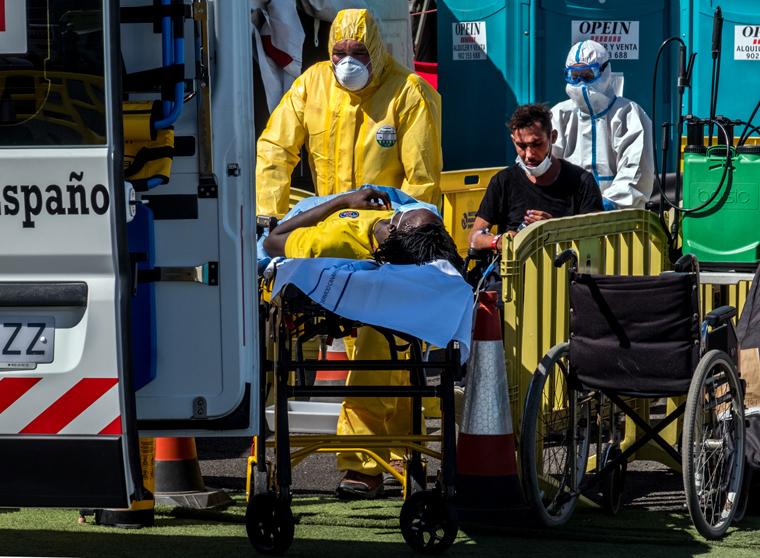 Sanitarios evacuan al hospital a dos personas migrantes tras desembarco en el muelle de Arguineguín, después de ser rescatados por Salvamento Marítimo. Fotografía: Javier Bauluz.