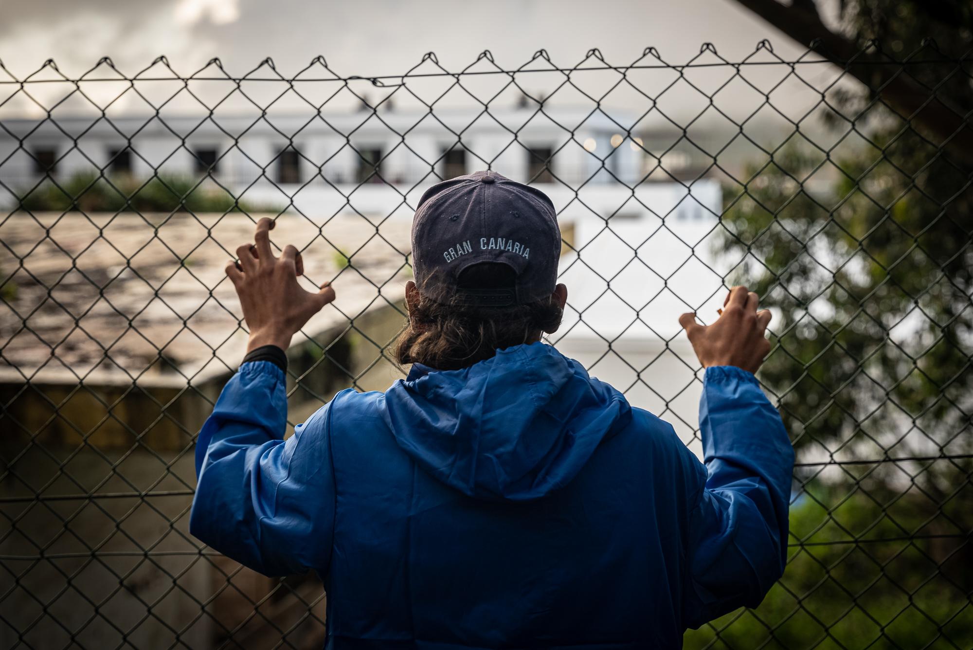 """Inmigrante en la verja del campamento """"Las Raíces"""" en Tenerife. Foto: Ignacio Marín."""