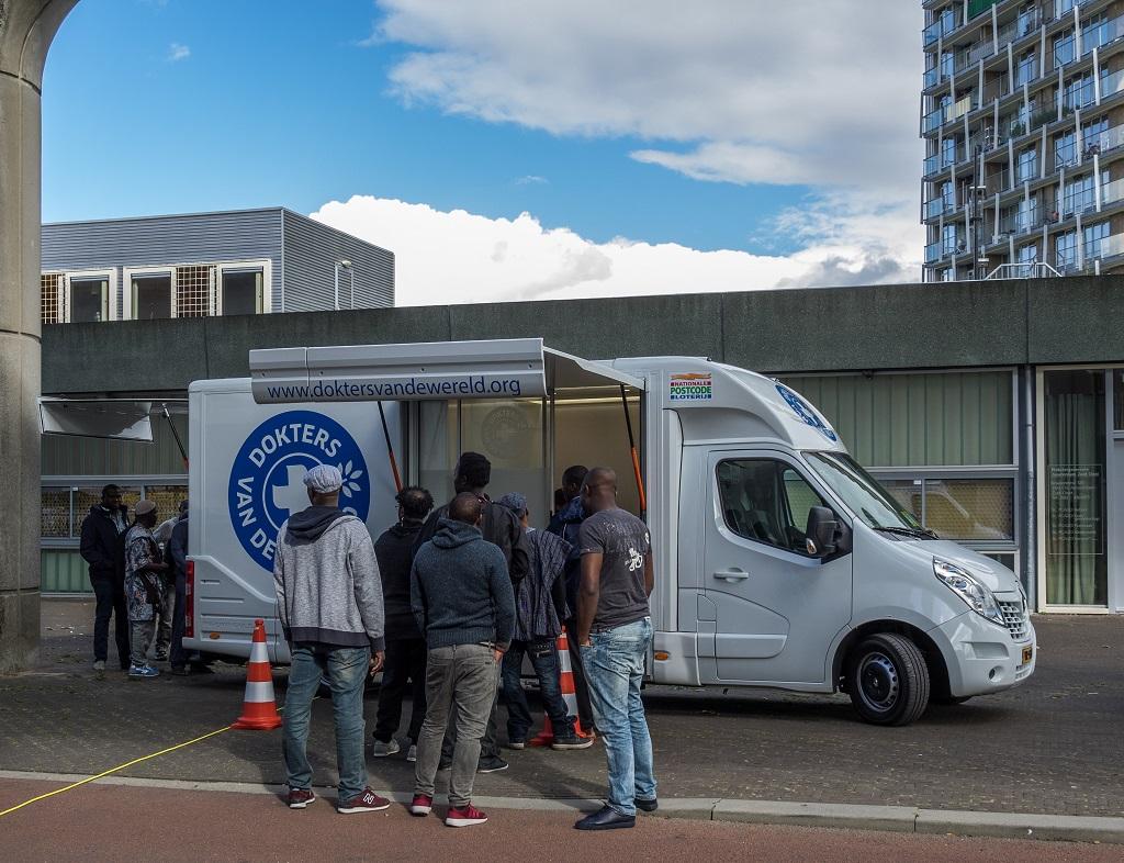 Un grupo de personas esperan para recibir atención médica en una unidad móvil. Foto: Esther van Nie