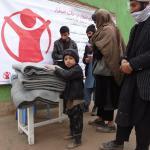 Un niño recoge mantas donadas por Save the Children en Afganistán.
