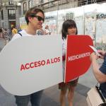 compañeras portando cartel-píldora reclamando acceso a los medicamentos