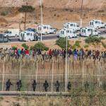 Personas inmigrantes encaramadas en la valla de Melilla