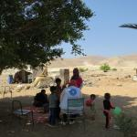 Imagen de una familia palestina junto a las ruinas de su casa demolida.