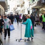 Una mujer en bata de hospital y con gotero simula pedir limosna en la calle para pagar la sanidad.