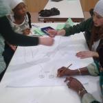 Mujeres del África Subsahariana y de España dibujan con lápices el perfil de un cuerpo femenino