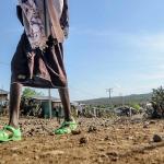 Un hombre camina sobre un terreno afectado por la sequía.