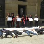 Un grupo de integrantes de la Plataforma Nasida escenifican ante el Palacio de Navarra el fallecimiento del Plan Nacional del Sida.