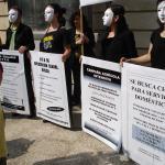 Varios activistas protestan frente a la Moncloa contra la trata de personas.