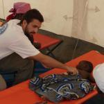 Un doctor, Javier Arcos, atiende a un niño en un Centro de Tratamiento de Cólera (CTC) en Cacuaco, Angola