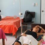 Una embarazada comparte una sala de la clínica con otra mujer que reposa junto a su bebé recién nacido en una cama.