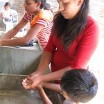 Una mujer enseña a su hijo cómo lavarse las manos.