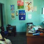 Pacientes en una sala de un centro de salud frente a un miembro del personal sanitario.