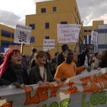 Varias personas protestan con pancartas frente a las instalaciones del CIE.