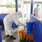 Desinfección de manos de personal del centro de aislamiento Nueva Kumala en Sierra Leona.
