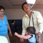 Un  niño es pesado con una báscula de techo por un sanitario. Su madre, observa la escena atentamente
