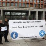 Miembros de Médicos del Mundo sostienen un cartel y las firmas de la Campaña Derecho a Curar frente a la entrada del Ministerio de Sanidad.