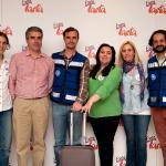 Personas con pegatinas de expotarta y los dos miembros de Médicos del Mundo con la de la ONG sonríen delante del panel lleno de pegatinas de expotarta
