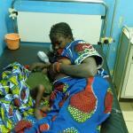 Fátima alimenta con suero a su hijo Bocar tumbada en una cama de la sala de pediatría.