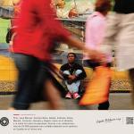 Un inmigrante angoleño, Antonio Joao, sentado en una calle mientras caminan varias personas.