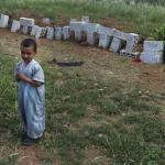 Un niño permanece de pié en un cementerio.