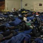 Inmigrantes duermen en el suelo tras su llegada al puerto de Calabria.