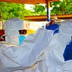 Proceso de vestido con traje de alta protección de sanitarios en el centro de aislamiento de Kasumpe, Sierra Leona.