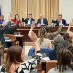 Varios diputados y varias diputadas levantan su mano para votar.