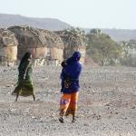Dos mujeres caminan junto a las tiendas de un campo de refugiados en Kenia.