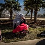 Refugiada sentada en el suelo llora mientras sostiene un bebé en el regazo.