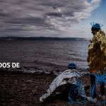 Tres refugiados se arropan con plásticos térmicos tras llegar a una playa Griega. Hay pintados tres sacos que parecen contener regalos en una imagen metafórica.