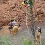 Dos mujeres en un depósito de agua estancada.