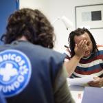 Una persona inmigrante sin tarjeta sanitaria revisa unos papeles en la consulta de Palma de Mallorca de Médicos del Mundo.