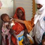 Personal sanitario de Malí ayuda a alimentarse a un bebé en brazos de su madre en el centro de salud del noroeste de Malí.