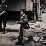 Un niño con un bolso cruza una calle, un policía lo mira y tras él hay un cadáver en la acera