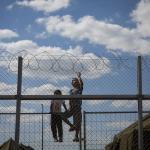 Unos niños se encaraman a una alambrada fronteriza