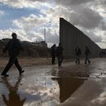 Paseantes en un dia nublado junto al muro de Cisjordania
