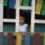 niña observando a través del hueco de una estructura