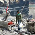 Un civil yemení andando sobre los escombros de un edificio