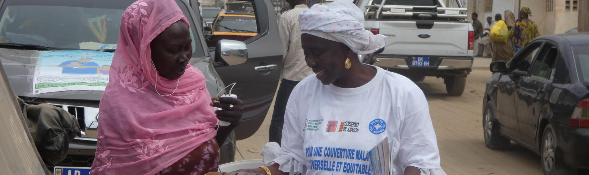 Una mujer reparte información para pedir una cobertura de salud universal e igualitaria en Senegal.