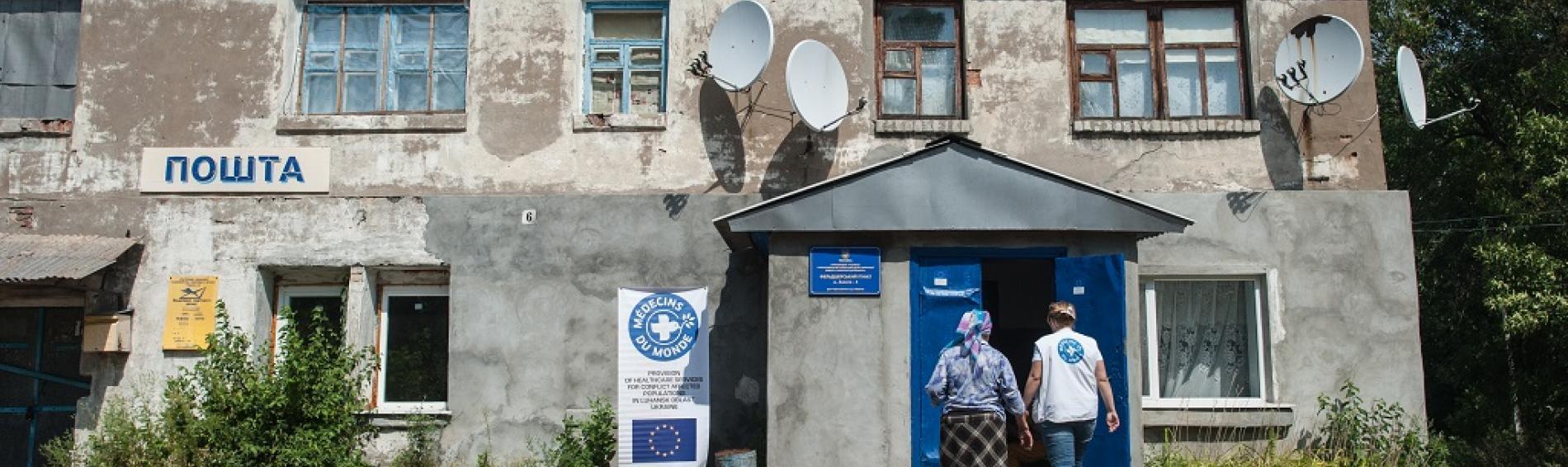 Una doctora y una anciana paciente se dirigen a la clínica de Médicos del Mundo en Luhansk