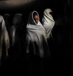 Migrantes cubiertos con mantas blancas tras el rescate.