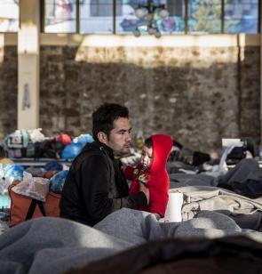 Refugiado con su hijo en un campo improvisado en la ciudad de Atenas