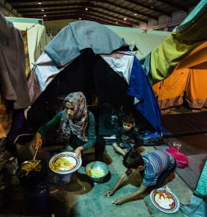 Una mujer cocina junto a dos niños frente a una tienda de campaña en un campo de refugiados griego.