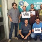 """Trabajadores de Médicos del Mundo ante la puerta de la sede central con el cartel """"Yo no soy putero""""."""