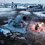 Persona refugiada se protege ante el frio invierno europeo en Serbia
